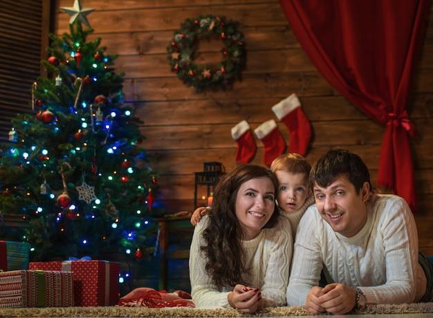 Familie mama, papa und sohn feiern weihnachten in einem geschmückten haus mit einem weihnachtsbaum