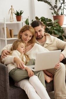 Familie mit baby, das laptop anschaut