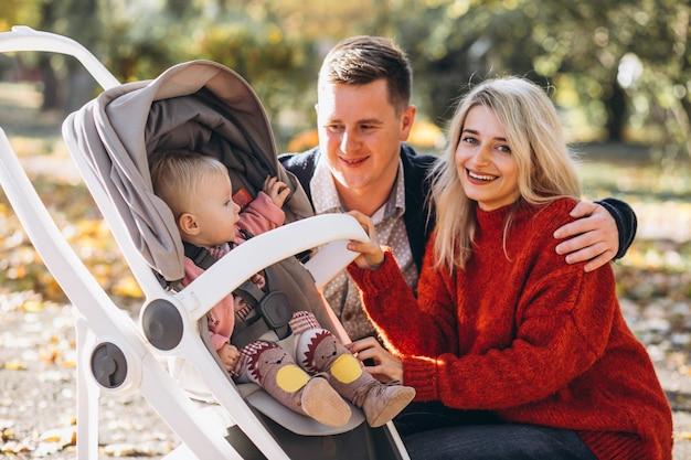 Familie mit baby daugher in einem kinderwagen gehend ein herbstpark