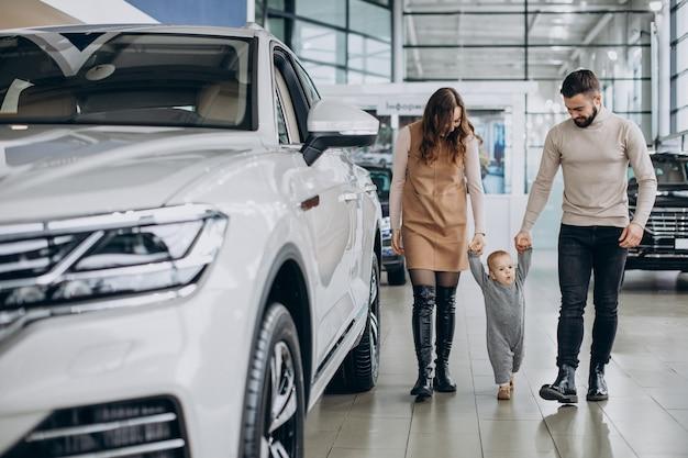 Familie mit baby, die ein auto in einem autosalon wählt