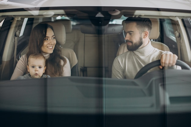 Familie mit bbay-mädchen, das ein auto in einem autosalon wählt