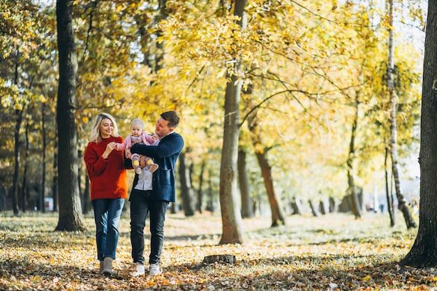 Familie mit dem baby daugher, das in einen herbstpark geht