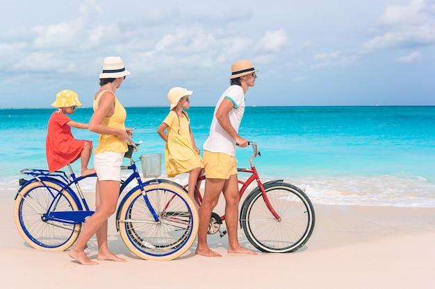 Familie mit dem fahrrad am tropischen strand