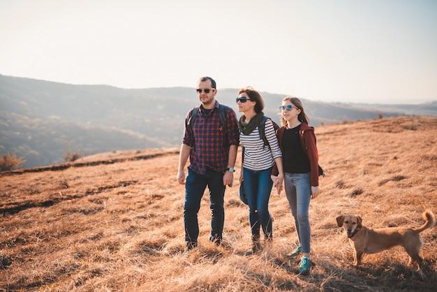 Familie mit dem hund, der auf einem berg wandert