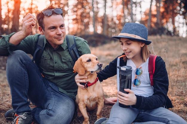 Familie mit dem hund, der im kiefernwald stillsteht