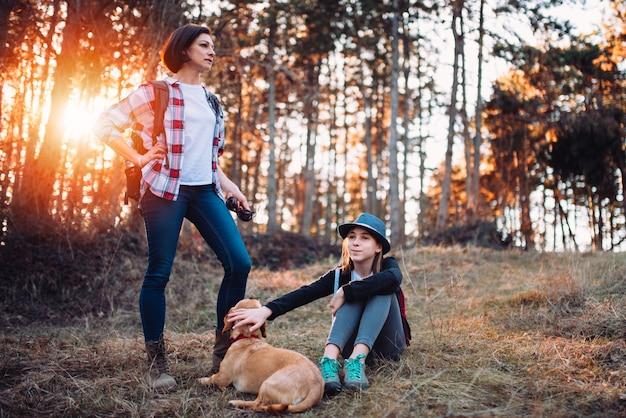 Familie mit dem hund, der im wald während des sonnenuntergangs stillsteht