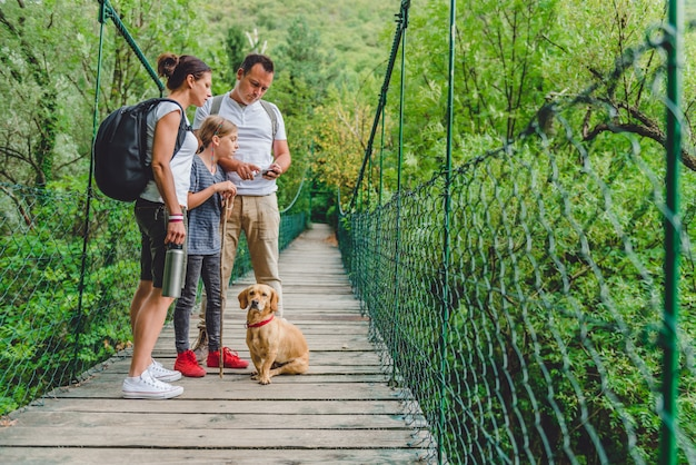 Familie mit dem hund, der im wald wandert