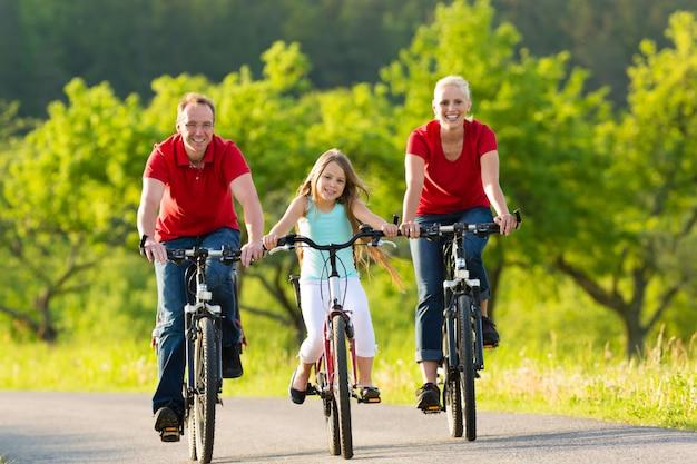Familie mit dem kind, das im sommer mit fahrrädern radfährt