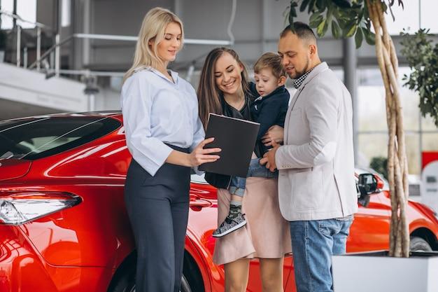 Familie mit dem sohn, der ein auto in einem autosalon wählt