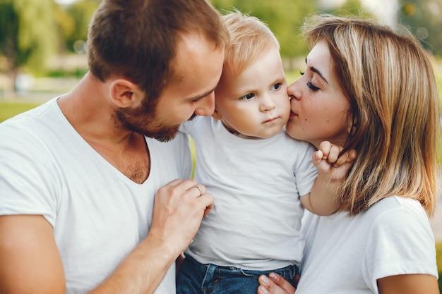 Familie mit dem sohn, der in einem sommerpark spielt