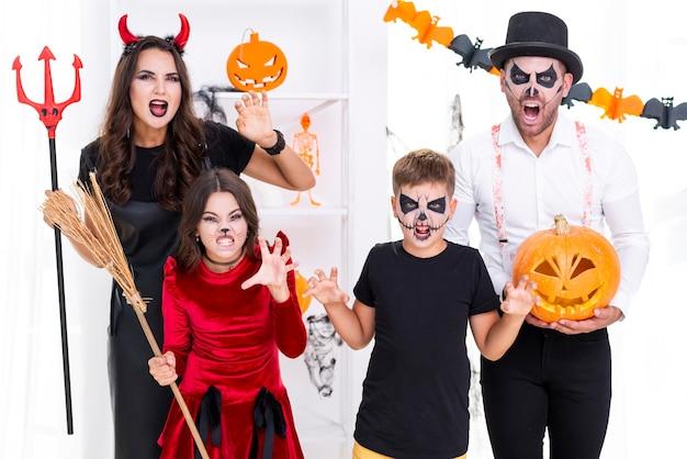 Familie mit den gemalten gesichtern, die für halloween aufwerfen
