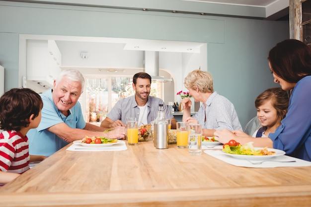 Familie mit den großeltern, die am speisetische sich besprechen