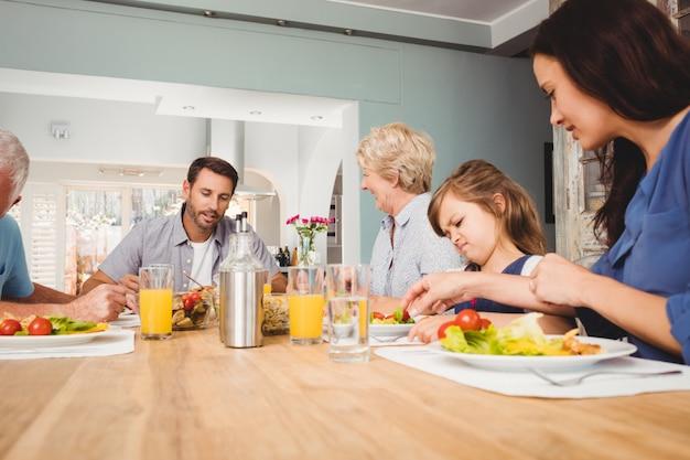 Familie mit den großeltern, die am speisetische sitzen
