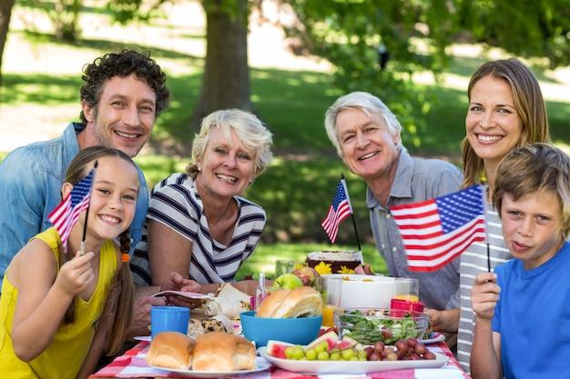 Familie mit der amerikanischen flagge, die ein picknick hat
