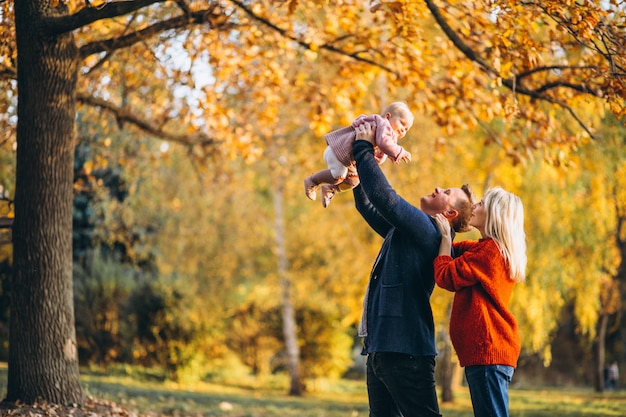Familie mit der babytochter, die in einen herbstpark geht