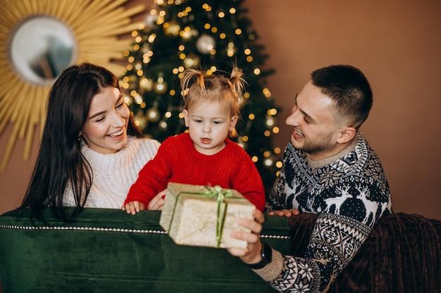 Familie mit der kleinen tochter, die durch weihnachtsbaum sitzt und geschenkbox auspackt