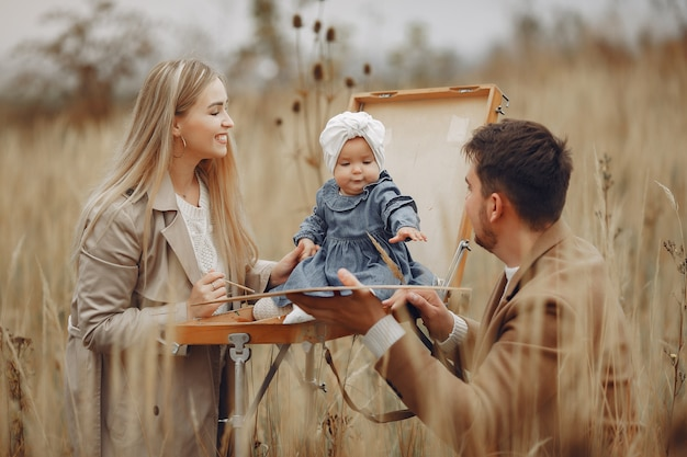 Familie mit der kleinen tochter, die in einem herbstfeld malt