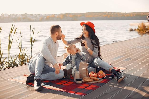 Familie mit der kleinen tochter, die nahe wasser in einem herbstpark sitzt
