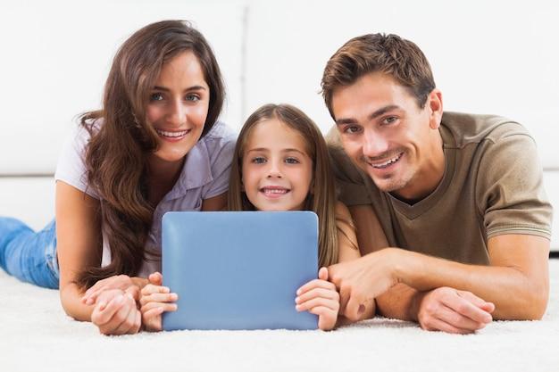 Familie mit der tablette, die auf einem teppich liegt