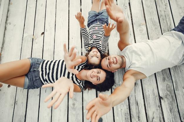Familie mit der tochter, die auf einem sand spielt