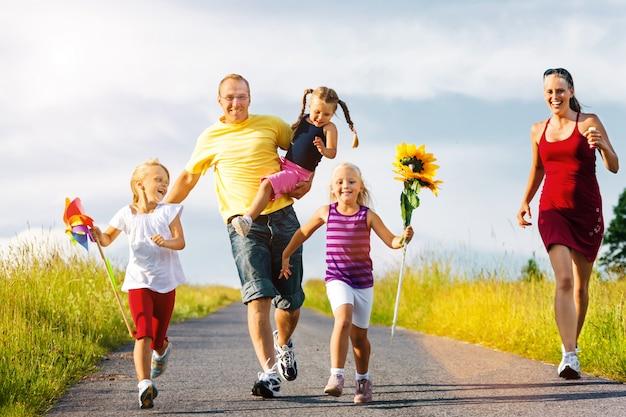 Familie mit drei kindern, die im sommer einen hügel hinunterlaufen
