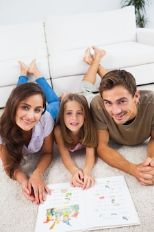Familie mit einem buch, das auf einem teppich liegt