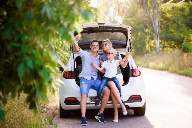 Familie mit einem kind, das im kofferraum eines autos sitzt und sich auf eine sommerreise zum meer vorbereitet