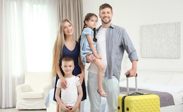 Familie mit gepäck im hotelzimmer