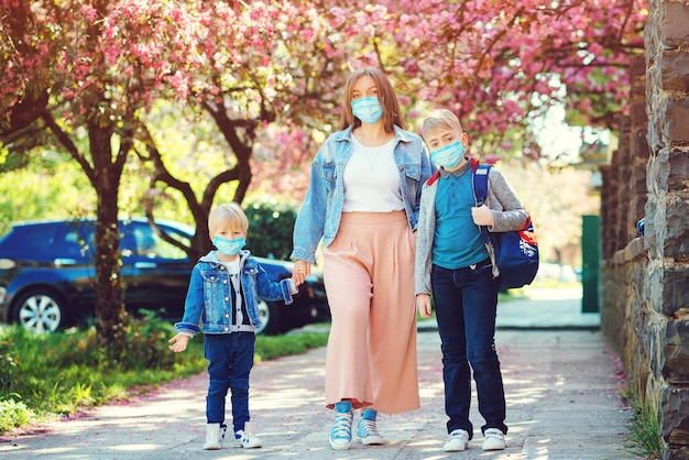 Familie mit gesichtsmasken. frühling. gesundheitskonzept. sicherheitsmaske gegen coronavirus. weltpandemie.