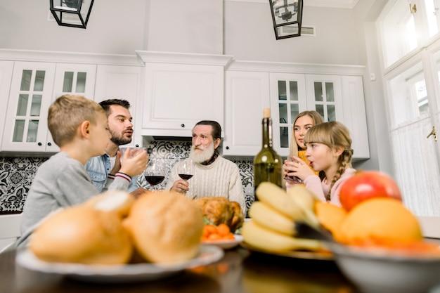 Familie mit großvater, der thanksgiving-mahlzeit am tisch genießt