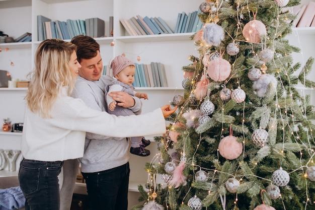 Familie mit hängenden spielwaren der kleinen tochter am weihnachtsbaum