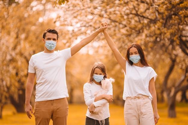 Familie mit hund, der medizinische schutzmaske trägt, um viren im freien im park zu verhindern