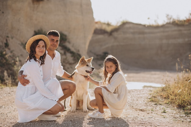 Familie mit ihrer tochter und ihrem hund, die hinausgehen