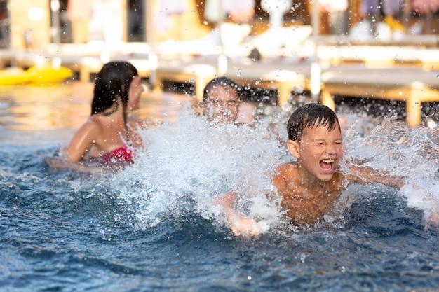 Familie mit jungen, die ihren tag im schwimmbad genießen