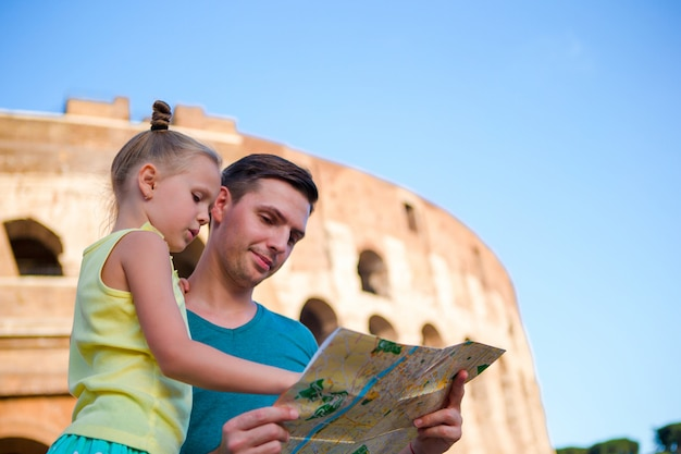 Familie mit karte vor dem kolosseum. vater und mädchen, die den anziehungskrafthintergrund der berühmte bereich in rom, italien suchen
