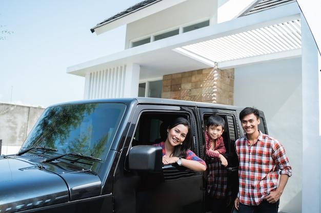Familie mit kind, das in einem auto im carport ihres hauses sitzt