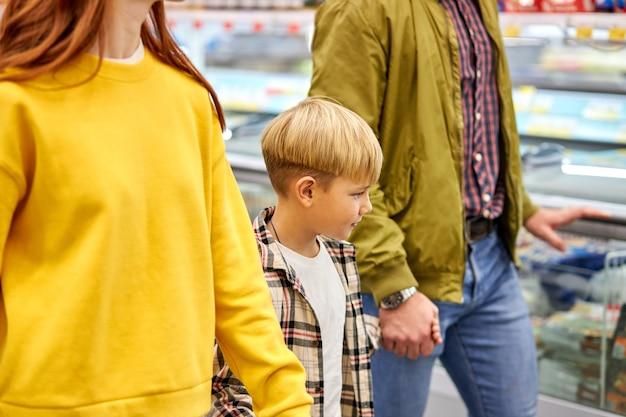Familie mit kind junge, die zusammen im lebensmittelgeschäft einkaufen, mann, frau und junge genießen, im supermarkt spazieren zu gehen, produkte zu kaufen, sie halten hände zusammen