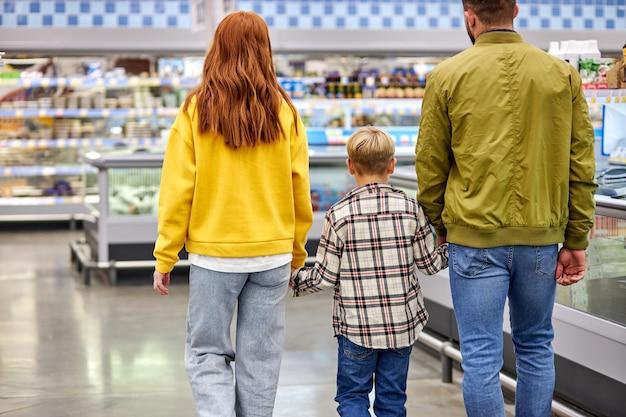 Familie mit kind junge einkaufen zusammen im lebensmittelgeschäft, mann frau und junge genießen im supermarkt spazieren gehen, produkte kaufen. rückansicht