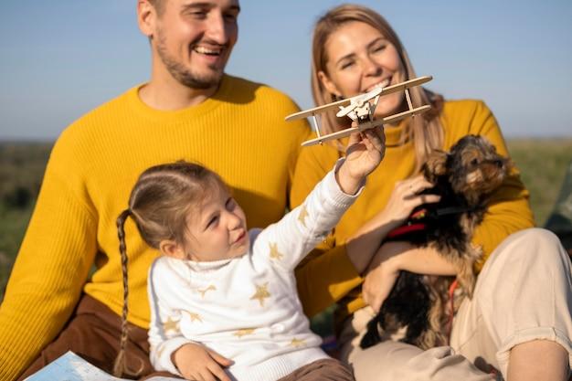 Familie mit kind und hund, die mit flugzeugspielzeug spielen
