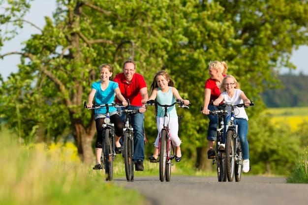 Familie mit kindern, die im sommer mit fahrrädern radfahren