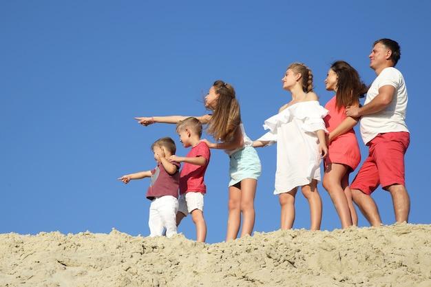 Familie mit kindern, die zusammen auf einem sandigen hügel stehen