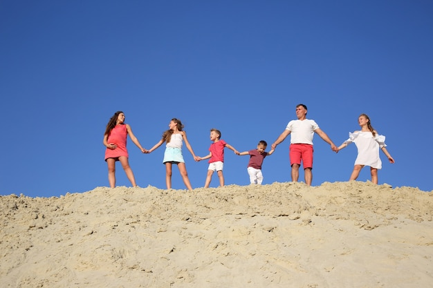 Familie mit kindern steht händchen haltend auf einem sandigen hügel