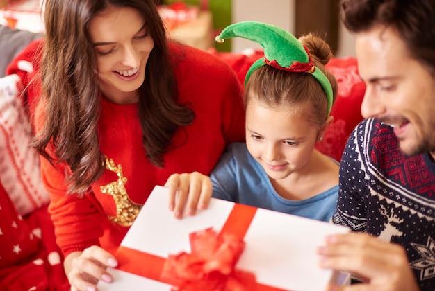 Familie mit kleinem mädchen, das weihnachtsgeschenk öffnet