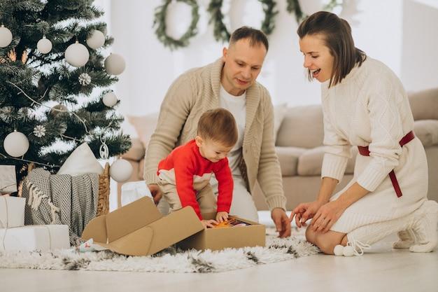 Familie mit kleinem sohn an weihnachten durch weihnachtsbaum zu hause