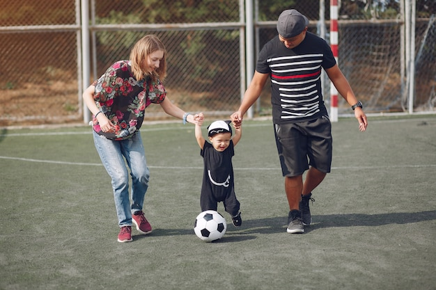 Familie mit kleinem sohn, der fußball spielt