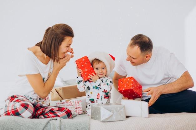 Familie mit kleinem sohn und weihnachtsgeschenken, die auf bett liegen