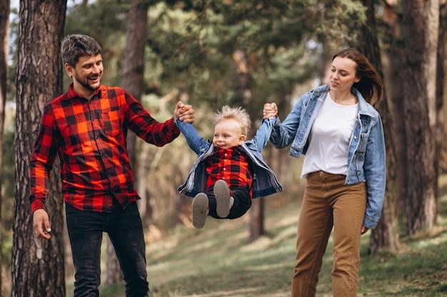 Familie mit kleinem sohn zusammen im wald
