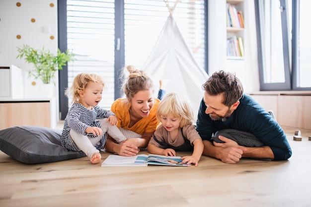 Familie mit kleinen kindern, die ein buch im schlafzimmer lesen