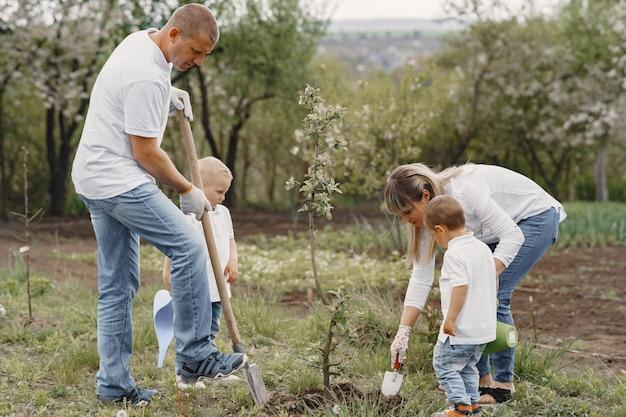 Familie mit kleinen söhnen pflanzt einen baum auf einem hof