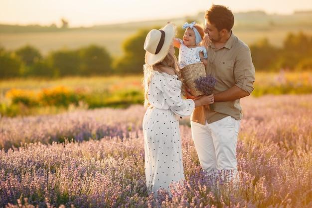 Familie mit kleiner tochter auf lavendelfeld. schöne frau und niedliches baby, das im wiesenfeld spielt. familienurlaub im sommertag.